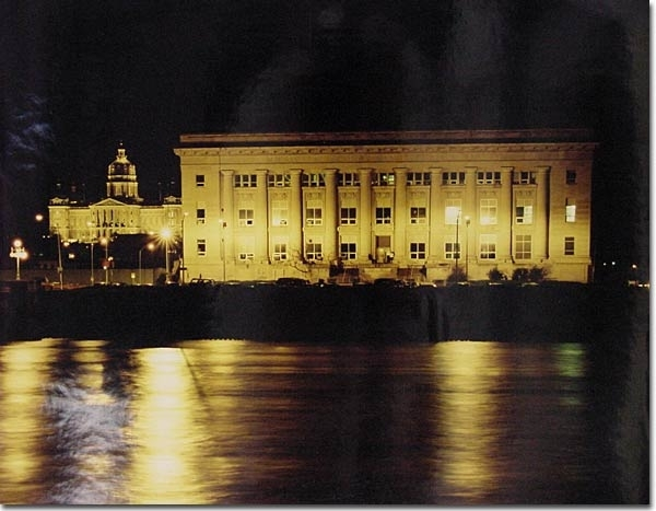 Night shot of Des Moines Police Department with Iowa State Capitol in background. Des Moines River in front.